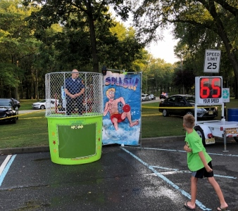 Ofc. Lang sitting in a dunk tank while local children attempt to dunk him