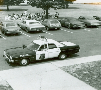 believed to possibly be a 1973 Plymouth Fury police car in front of then Applegarth Middle School The building is now Applegarth Elementary School