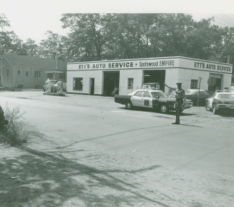 Photo of a Monroe Police Officer directing traffic on the corner of Spotswood Englishtown Road and Harrison Avenue in front of Ett's Auto Service This building is now home to Royal Transmissions